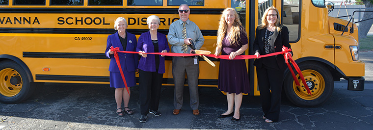 Board Members and Superintendent in front of school bus with ribbon